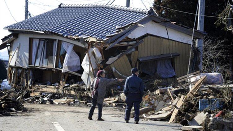Des retraités regardent une maison déplacée après le tsunami, à Minamisoma, le 12 mars 2011. (AFP PHOTO / KAZUHIRO NOGI)
