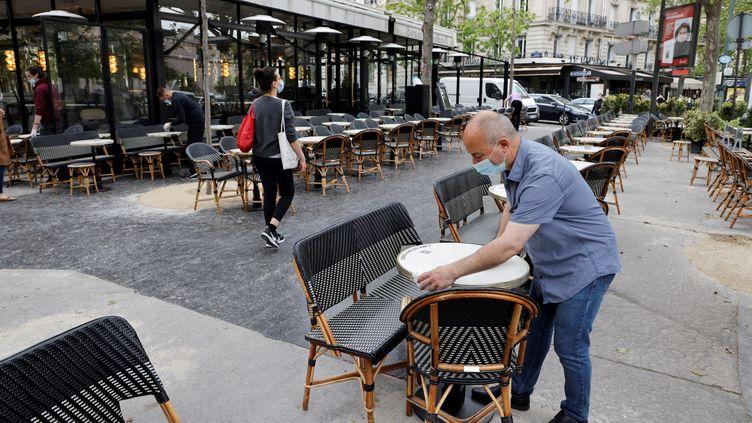 Un employé d'un café parisien nettoie les tables de la terrasse extérieure, le 11 mai 2021. (LUDOVIC MARIN / AFP)