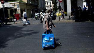 Un homme porte un sac dans une rue d'Athènes (Grèce) le 11 juillet 2015. (ANGELOS TZORTZINIS / AFP)