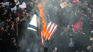 Des manifestants iraniens brûlantdes drapeaux américain et israélien, le 6 janvier 2020, à Téhéran. (ATTA KENARE / AFP)