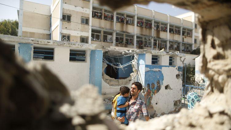 Un homme évacue un enfant après la destruction d'une école de l'ONU servant de refuge pour les palestiniens, le 30 juillet 2014 à Gaza. (© SUHAIB SALEM / REUTERS / X90014)