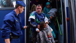Un policier hongrois aide des migrants à descendre d'un bus à Roszke, le 15 septembre 2015. (ATTILA KISBENEDEK / AFP)