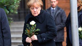 La chancelière allemande, Angela Merkel, dépose une fleur, le 20 décembre 2016, aumarché de Noël de Berlin(Allemagne),visé la veille par un attentat meurtrier. (MAURIZIO GAMBARINI / ANADOLU AGENCY / AFP)