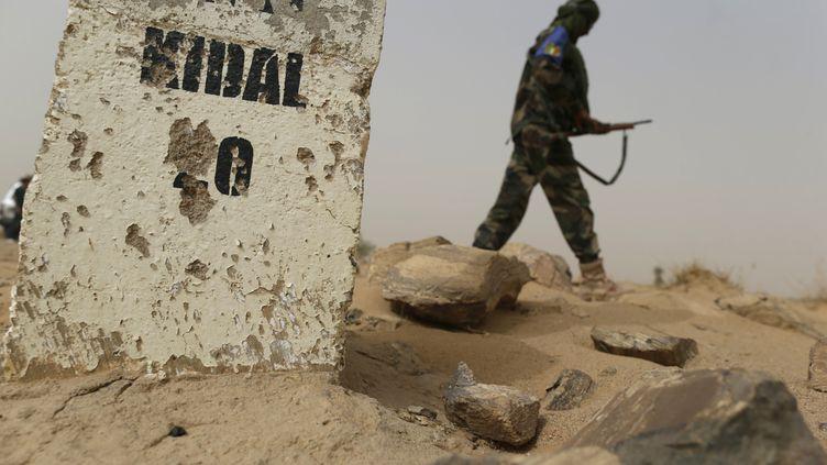 Un soldat malien patrouille sur une route près de Kidal (Mali), où les deux journalistes français de RFI ont été assassinés le 2 novembre 2013. (KENZO TRIBOUILLARD / AFP)