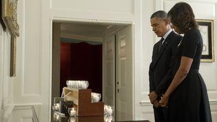 Barack Obama et son épouse Michelle observent une minute de silenceen hommage aux 26 victimes, dont 20 enfants, de la fusillade de l'école Sandy Hook de Newtown, à la Maison Blanche, à Washington (Etats-Unis), le 14 décembre 2013. (SAUL LOEB / AFP)