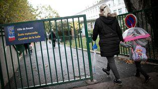 Une femme et un enfant arrivent le 30 septembre 2019 à l'école maternelle Cavelier de la Salle, une des deux écoles de Rouen où des traces de suie ont été retrouvées sur des rebords de fenêtres. (LOU BENOIST / AFP)