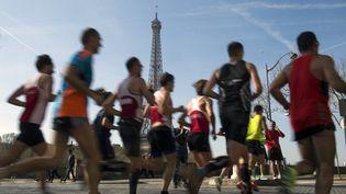 Des coureurs en plein effort près de la tour Eiffel, lors du Marathon de Paris, le 12 avril 2015. (VALERIY MELNIKOV / RIA NOVOSTI / AFP)