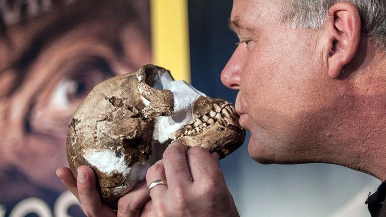 """Le professeur Lee Berger embrasse la copie du crâne """"d'Homo naledi"""" lors de la conférence de presse à Maropeng, en Afrique du sud, le 10 septembre 2015, où a été dévoilé ce qui serait une nouvelle espèce humaine. (STEFAN HEUNIS / AFP)"""