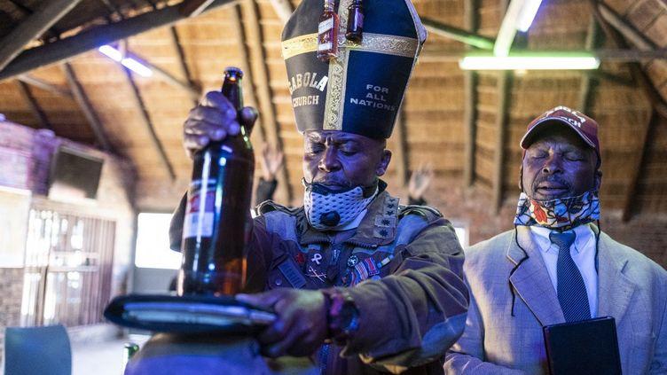 Tsietsi Makiti, fondateur de l'Eglise Gabola, en plein rituel dominical (avec sa mitre décorée de 2 mignonettes d'alcool), à la Bunny's Tavern d'Evaton en Afrique du Sud. (WIKUS DE WET / AFP)