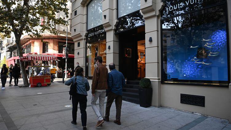 Des passants devant une boutique de la marque française Louis Vuitton, à Istanbul (Turquie) le 26 octobre 2020 (OZAN KOSE / AFP)