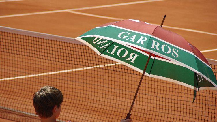 Un ramasseur de balles tenant un parapluie pour faire de l'ombre sur un court de Roland-Garros, porte d'Auteuil à Paris. Photo d'illustration. (PIERRE NEVEUX / RADIO FRANCE)