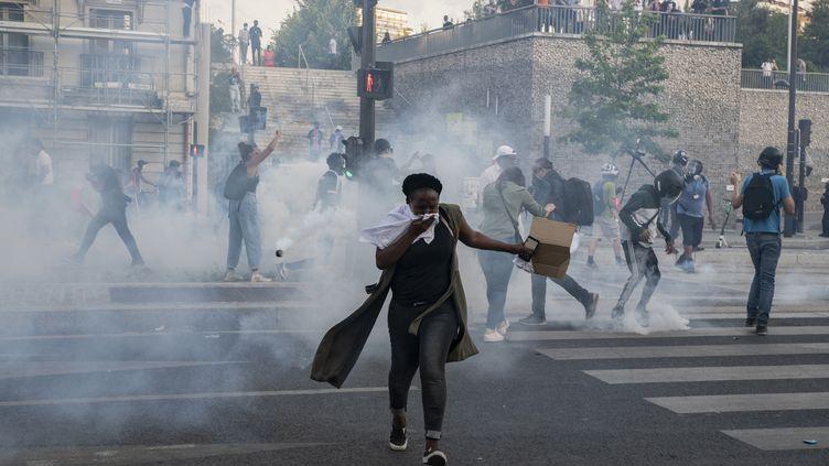 Une femme s'éloigne du gaz lacrymogène libérépar les forces de l'ordre près du Tribunal de Paris après la manifestation du comité Vérité et Justice pour Adama Traoré, le 2 juin 2020, quelques jours après le meurtre del'Afro-Américain George Floyd. (ANTONI LALLICAN / HANS LUCAS / AFP)