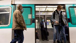 Des passagers masqués descendent du métro à Paris, le 5 novembre 2020. (MARTIN NODA / HANS LUCAS / AFP)
