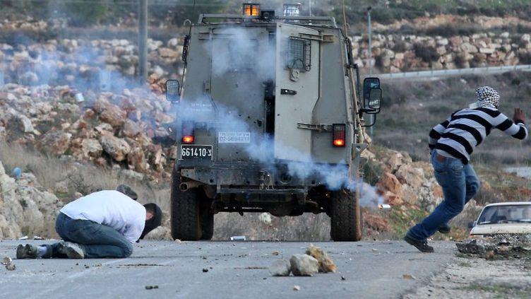 Le manifestantMoustapha Abderrazek al-Tamimi, à gauche, prostré avoir reçu une grenade lacrymogène au village de Nabi Saleh (Cisjordanie), le 9 décembre 2011. (HAIM SCHWARCZENBERG / AFP)