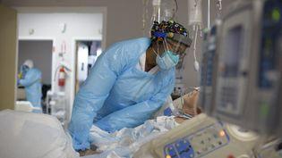 Une membre du personnel soignant au chevet d'un malade du Covid-19, à Houston (Texas, Etats-Unis), le 4 décembre 2020. (MARK FELIX / AFP)