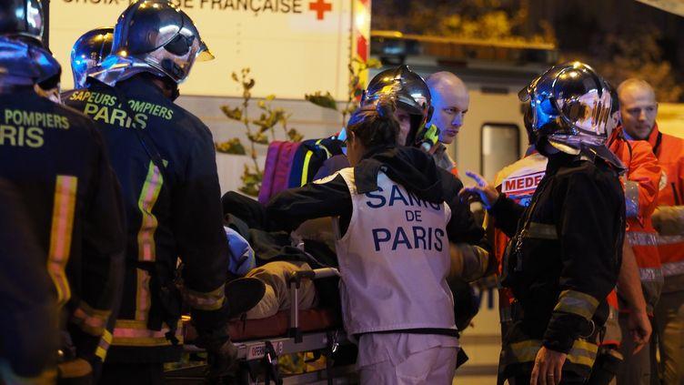 Les secours évacuent des victimes de l'attaque perpétrée devant le restaurant Le Petit Cambodge, le 14 novembre 2015 à Paris. (MUSTAFA YALCIN / ANADOLU AGENCY / AFP)
