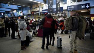 Des passagers dans la gare Montparnasse, touchée par une panne géante, le 3 décembre 2017 à Paris. (MARTIN BUREAU / AFP)