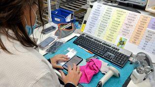 Une salariée reconditionne un smartphone, en octobre 2020. (MICHAEL ESDOURRUBAILH / MAXPPP)