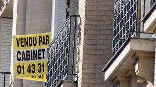 Panneau de vente posé sur la rambarde d'une fenêtre. (ERIC PIERMONT / AFP)