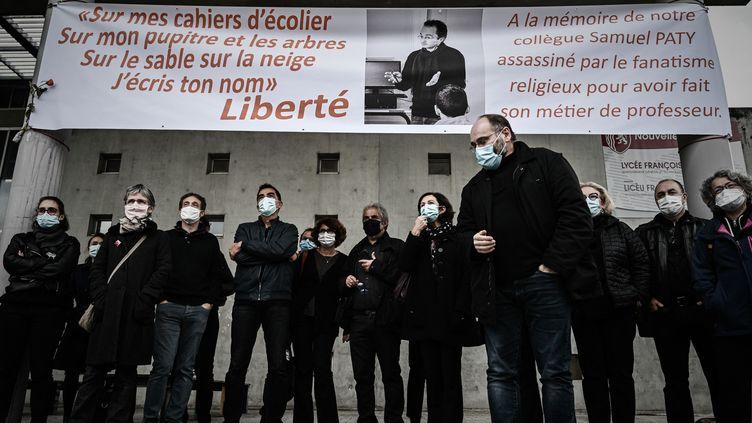 Des professeurs de lycée habillés en noir regardent une banderole qu'ils ont déployée en hommage au professeur d'histoire français assassiné Samuel Paty au lycée François-Magendie de Bordeaux le 2 octobre 2020. (PHILIPPE LOPEZ / POOL)