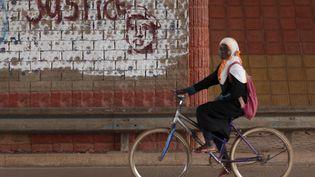 """Une jeune fille passe devant un graffiti où on peut lire """"justice"""" à côté du visage de Thomas Sankara, à Ouagadougou, capitale du Burkina Faso, le 4 décembre 2015. (JOE PENNEY / X02952)"""