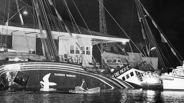 Le Rainbow Warrior couché sur le côté dans le port d'Auckland, le 10 juillet 1985. (AFP / New Zealand Herald)