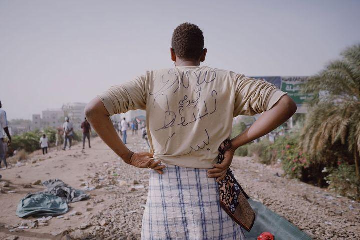 """Muhammad Salah. Un manifestant dont l'inscription au dos de sa chemise signifie """"Un révolutionnaire de Kalakla, une chute, c'est tout"""" ; il se tient sur la ligne ferroviaire centrale de Khartoum qui faisait partie de la zone de sit-in du QG de l'armée. Khartoum, Soudan, 13 avril 2019. (-)"""