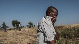 Un homme en larmesdevant une fosse commune où sont entassés les corps d'au moins 20 victimes d'un massacre qui a eu lieu près de Mai Kadra (Ethiopie), le 9 novembre 2020. (EDUARDO SOTERAS / AFP)