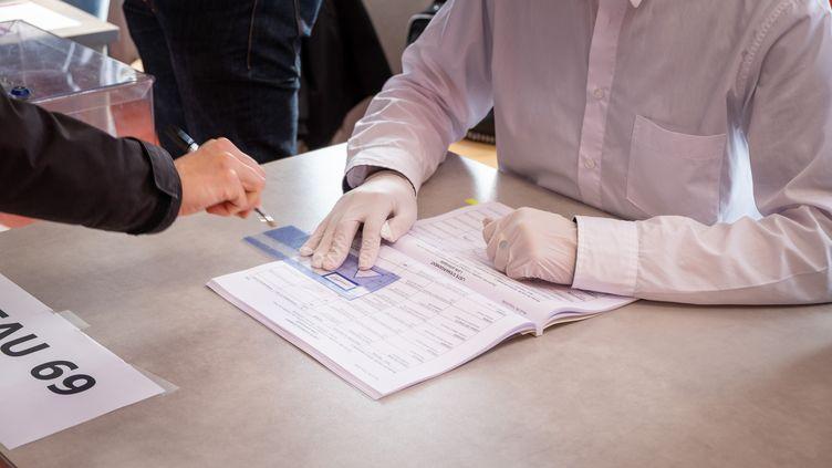Une personne émarge après avoir voté, à Toulouse (Haute-Garonne), le 15 mars 2020. (ADRIEN NOWAK / HANS LUCAS)