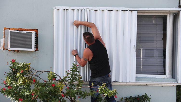Un homme barricade une fenêtre à l'approche de l'arrivée de l'ouragan Isaias, à Lake Worth (Floride, Etats-Unis), vendredi 31 juillet 2020. (JOE RAEDLE / GETTY IMAGES NORTH AMERICA / AFP)