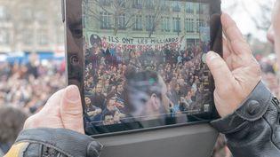 Un homme filme la mobilisation place de la République à Paris, le 3 avril 2016. (CITIZENSIDE /DIDIER LABASTE / AFP)