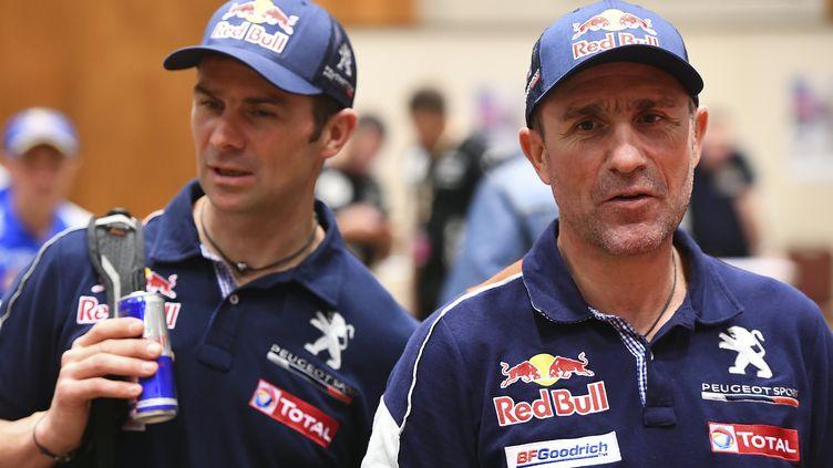 Les pilotes Peugeot Cyril Despres et Stéphane Peterhansel participe à une réunion d'avant-course, le 31 décembre 2016, à Asuncion (Paraguay). (FRANCK FIFE / AFP)