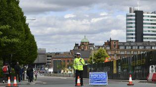 Un officier de police surveille les abords de la salle où un attentat a eu lieu, à Manchester, au lendemain du drame, le 23 mai 2017. (BEN STANSALL / AFP)