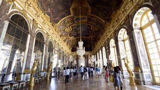 Des visiteurs parcourent la Galerie des glaces, le 24 juin 2014, dans le château de Versailles (Yvelines). (BERTRAND GUAY / AFP)