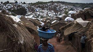 Une Congolaise traverse un camp de déplacés internes le 20 mars 2018 à Kalemie, en République démocratique du Congo.Un conflit en cours entre les Pygmées et Bantous a déplacé 67.000 personnes autour de Kalemie et selon les agences humanitaires jusqu'à 650.000 personnes au plus fort de la crise dans la province du Tanganyika. (John WESSELS / AFP)