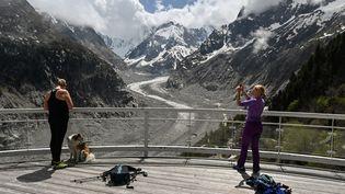 Des touristes face à la Mer de glace du Mont Blanc, près de Chamonix (Haute-Savoie), le 16 mai 2020. (PHILIPPE DESMAZES / AFP)