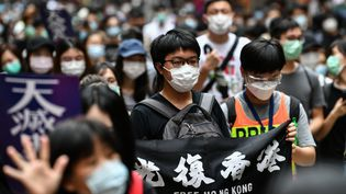 """Un opposant à l'influence de Pékin porte une pancarte invitant à """"libérer"""" Hong Kong, dimanche 24 mai 2020, dans le centre de l'île de Hong Kong. (ANTHONY WALLACE / AFP)"""