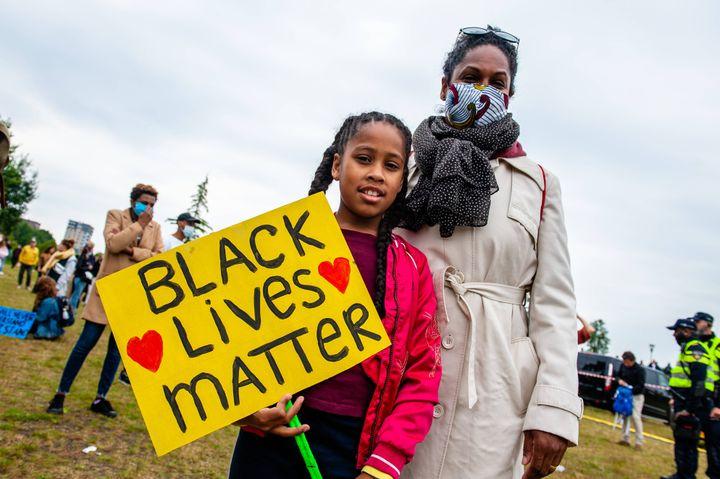 """Une femme et sa fille portent une pancarte """"Black lives matter"""", lors d'un rassemblement à Amsterdam (Pays-Bas), le 10 juin 2020. (ROMY FERNANDEZ/SIPA USA/SIPA)"""