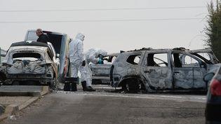 Des policiers inspectent des véhicules carbonisés après un braquage à Dardilly (Rhône), le 12 décembre 2016. (MAXPPP)