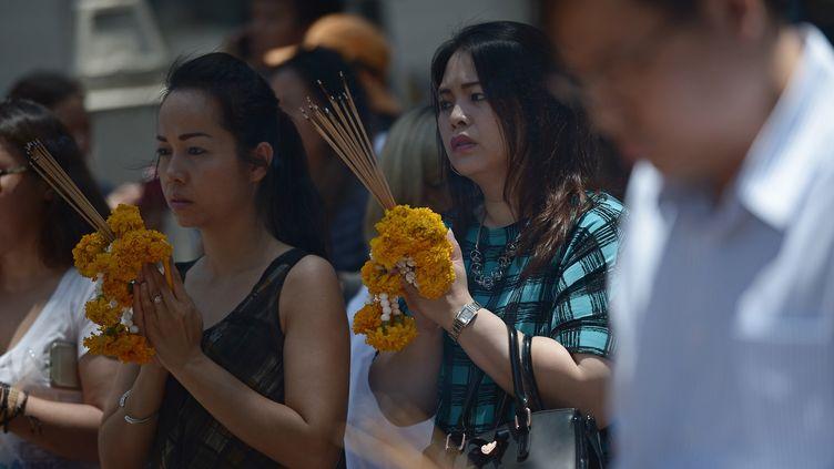 Des personnes prient lors de la réouverturedu sanctuaire visé par un attentat à Bangkok (Thaïlande), le 19 août 2015. (CHRISTOPHE ARCHAMBAULT / AFP)