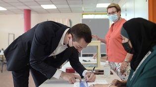 Jordan Bardella signe le registre après avoir déposé son bulletin de vote dans un bureau de Saint-Denis, lors du 1er tour des élections régionales (20 juin 2021). (LUCAS BARIOULET / AFP)