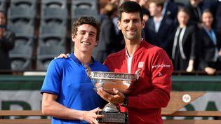 Le Français Geoffrey Blancaneaux, vainqueur du tournoi juniors, pose avec le gagnant de l'épreuve chez les pros, Novak Djokovic, en juin 2016 (PHILIPPE LOPEZ / AFP)