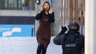 Une otage court en direction d'un policier après être sortie du café du centre-ville de Sydney (Australie) où plusieurs personnes sont toujours retenues par un homme armé, lundi 15 décembre. (JASON REED / REUTERS)