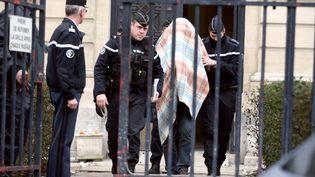 Caché sous une couverture, Willy Bardon, entouré de gendarmes devant le palais de justice d'Amiens (Somme), le 18 janvier 2013. (PHILIPPE HUGUEN / AFP)