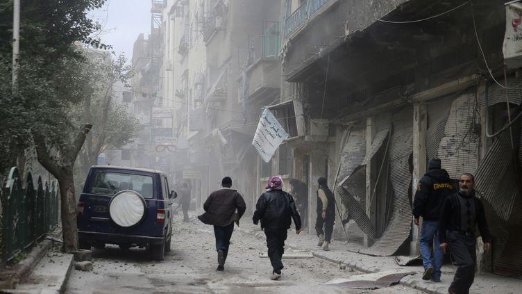 Des habitants courent dans les rues d'un faubourg de Damas, après un bombardement, le 12 décembre 2013. (MOHAMED ABDULLAH / REUTERS)