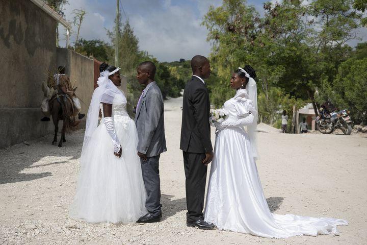Patricia, enceinte, et Obelson se sont mariés au cours d'une cérémonie collective. Ils posent devant l'église avec un autre couple qu'ils ne connaissent pas (VALERIE BAERISWYL)