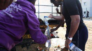 Des migrants lors d'une distribution d'eau, en juin 2017, à Calais. (OLIVIER ARANDEL / MAXPPP)