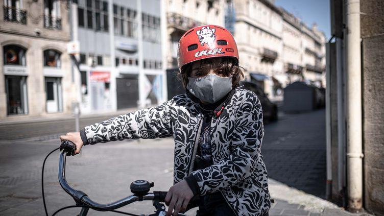 Un enfant à vélo, portant un masque de protection, à Bordeaux, le 5 avril 2020, lors de l'épidémie de coronavirus. (FABIEN PALLUEAU / NURPHOTO / AFP)