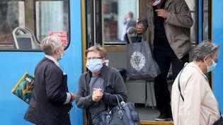 Des Croates portent un masque contre le Covid-19 à Zagreb, le 26 octobre 2020. (STIPE MAJIC / ANADOLU AGENCY / AFP)