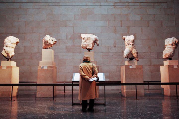 Une visiteuse du British Museum admire lessculptures du Parthénon d'Athènes, le 13 février 2020. (DAVID CLIFF / NURPHOTO / AFP)